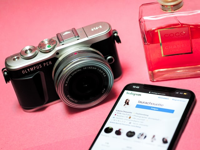 picture of a camera, Chanel perfume bottle, and smart phone with Instagram influencer on the screen.