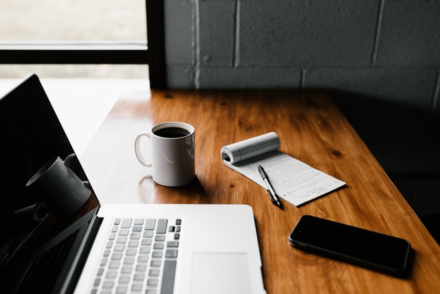 photo of a laptop, notebook, pen, cellphone, and cup of coffee on a wooden table for content marketing ideas.