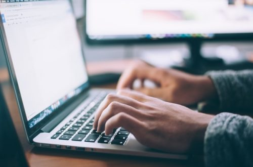 Photo of a person typing on a laptop to write content.