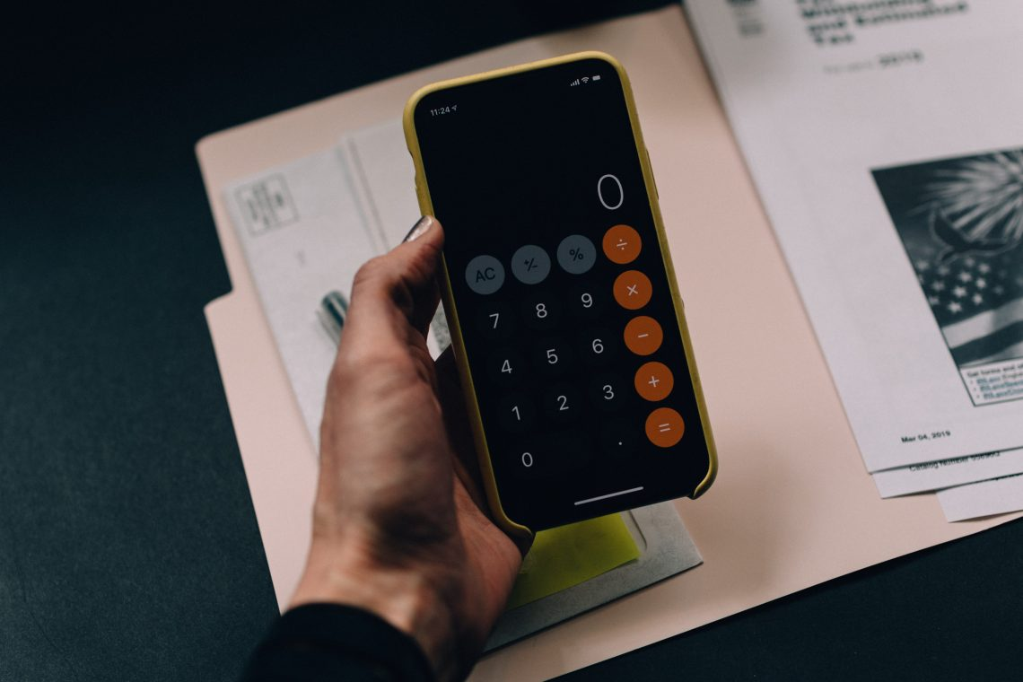 photo of someone holding a calculator over a documents to calculate marketing budget.