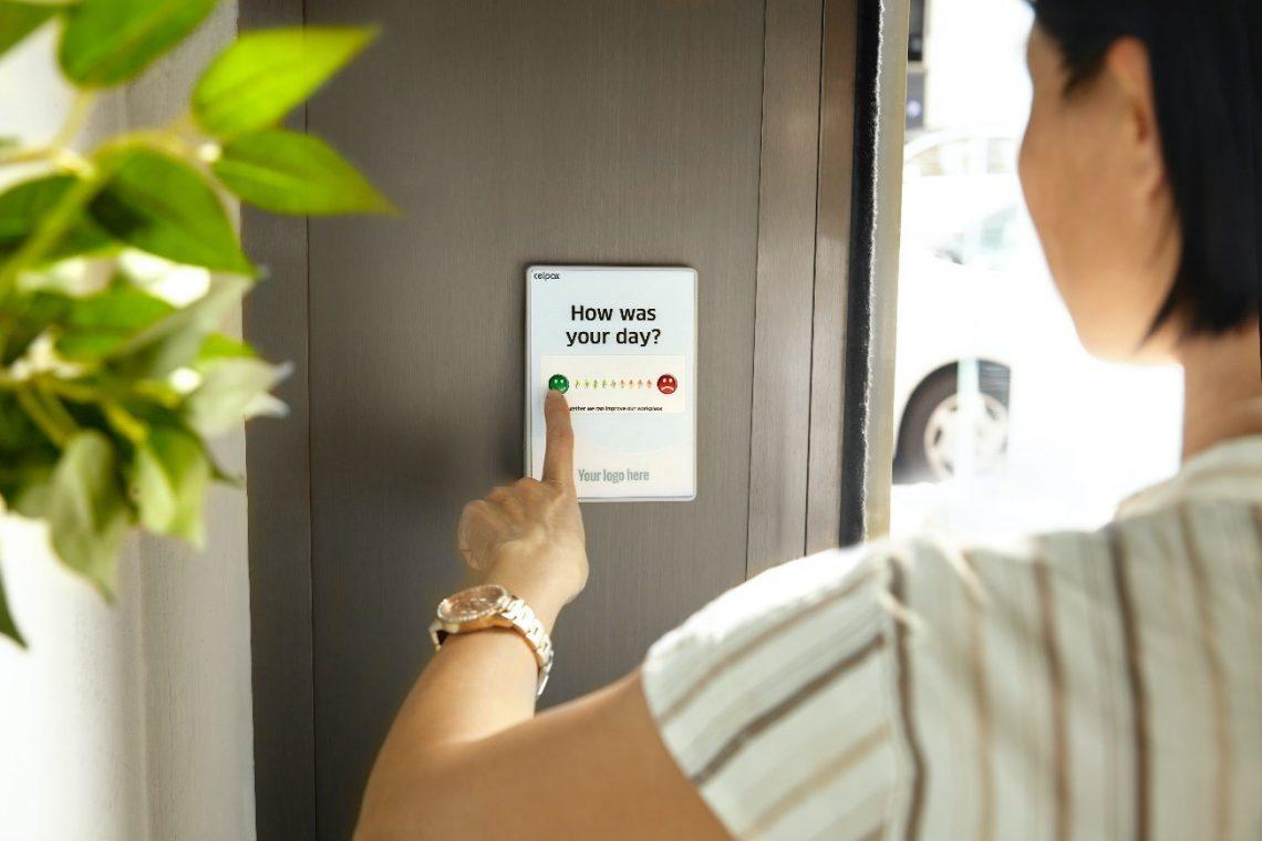 Woman choosing a response on a survey on a door.