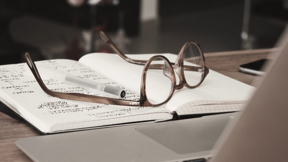 glasses, pen, and notebook on top of a desk.