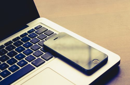 side profile of a phone and laptop on a desk.