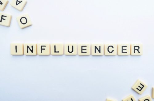 """scrabble letters spelling the word """"influencer"""" on a white background."""