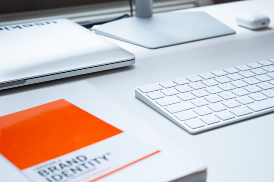 """a white desktop computer and keyboard with an orange and white book titled """"Brand Identity"""" sitting on a white table."""