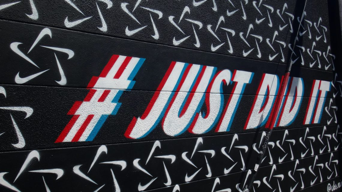 """a hashtag of Nike's """"Just Do It"""" slogan on a black background."""