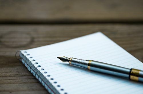 a notebook and pen sitting on top of a wooden table.